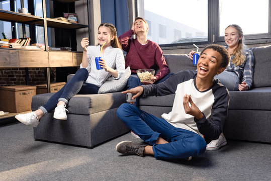 Happy group of teenagers watching movie together at home, teenagers having fun concept