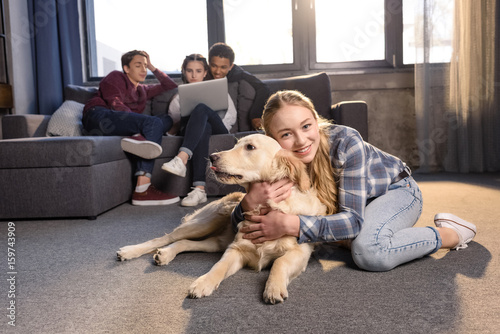 Smiling Teenage Girl Having Fun With Golden Retriever Dog While