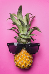 small ripe pineapple with sunglasses on a bright pink background, fashion photography top view close up