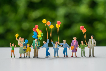 Miniature people with family holding balloon with green color background as happy family concept