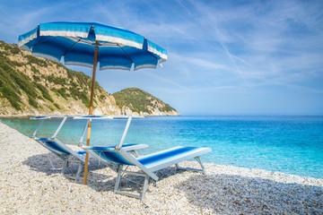 Wall Mural - Two lounge chairs with sun umbrella on a Sansone beach, Elba Island, Tuscany, Italy.