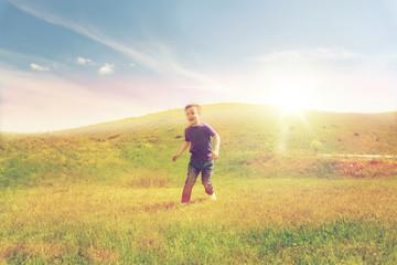 happy little boy running on green field outdoors