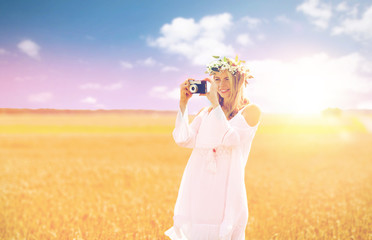 happy woman with film camera in wreath of flowers