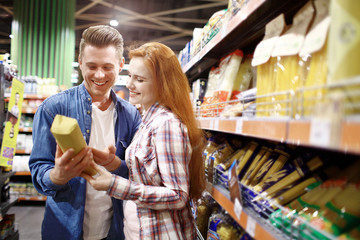 young couple chooses foods at the supermarket