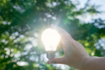 Woman hands holding light bulb with solar energy or thermal energy concept.