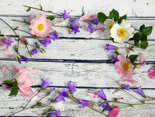 Bellflower flowers, wild rose and pink petals on a wooden background, rustic style