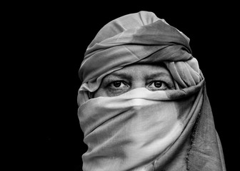 Strong portrait of a middle aged woman wearing a Moroccan shesh, a Touareg turban.