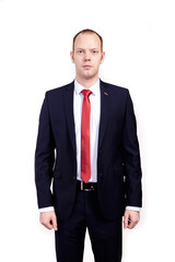 Respectable senior businessman, wearing black suit, white shirt and red tie standing on white background