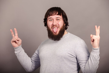 Young funny man with long beard sticking out his tongue isolated on the dark background
