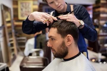 man and barber cutting hair at barbershop