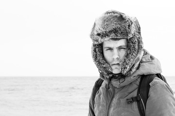 Portrait Of Man Wearing Hooded Shirt Standing Against Sea