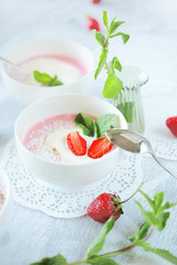 Cold creamy strawberry soup with a scoop of ice cream and mint