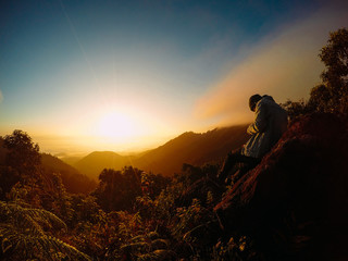 Alone man on the top of the mountains. He shooting cloudy sky and colorful sunrise.
