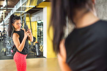 Sporty girl with smartphone taking mirror selfie in gym.