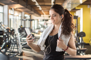 Sporty woman with earphones using smartphone to listen favorite songs in gym.
