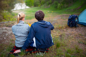 Romantic couple resting near the lake, summer forest background. Young blonde woman and handsome man. Camping, travel, tourism, hike and people concept