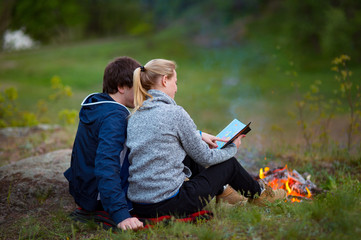 Couple hiking. Young couple sitting on grass near the fire embracing and examining the map. Travel, vacation, holidays and adventure concept. Forest Mountain landscape background