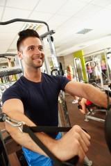 Happy man training in gym