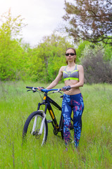 A young woman is standing with a bicycle in the forest. A sporty woman, a healthy lifestyle.