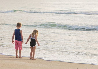 Boy (6-7) and girl (4-5) standing on beach by water