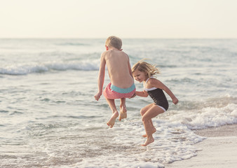 Boy (6-7) and girl (4-5) jumping in water on beach