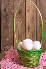 White eggs in the green basket on wooden background