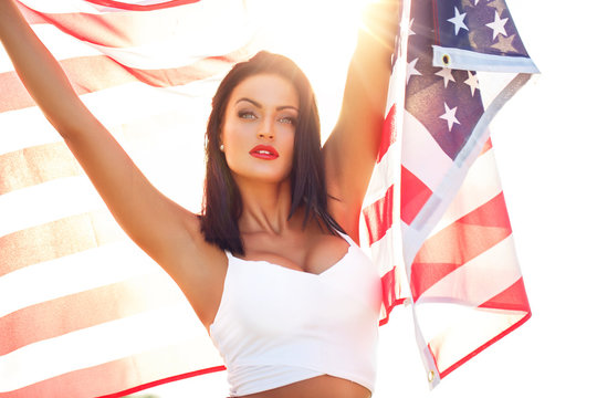 Sexy young woman holding star spangled banner USA flag