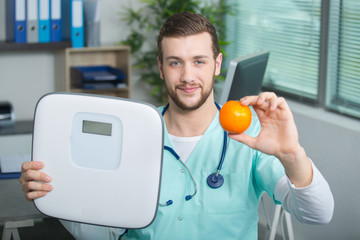 doctor with fruit and bathroom scales