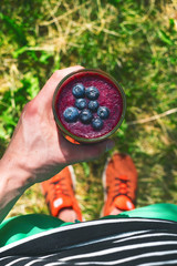 Smoothie drink a sport man in a nature. Glasses of smoothie with berry and mint. Berry, leaf and lime, raspberriesFruit Healthy food. Take a way breakfast.