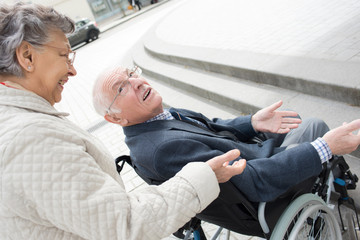 old woman walking outdoors with his husband in wheelchair