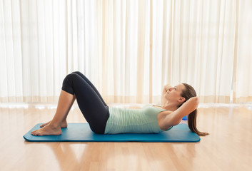 Woman doing sit up exercise indoors.