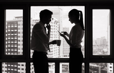Businessman and businesswoman having a conversation at work.