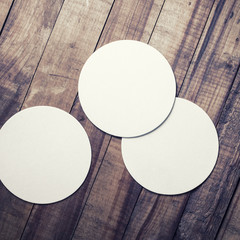 Three blank beer coasters on vintage wooden table background. Responsive design mockup. Top view.
