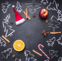 chalk board with painted Christmas decorations, Christmas trees, candy, cups and ingredients for mulled wine, tiled frame, space for text, top view