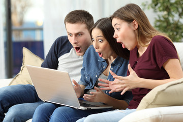 Amazed friends watching content on line in a computer