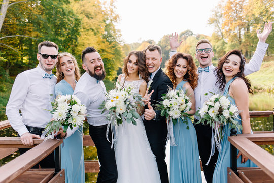 Positive, stylish guests at the wedding together with the couple in love laugh and pose on the camera