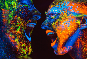 Concept. Couple smiling. Portrait of a pair of lovers painted in fluorescent powder.