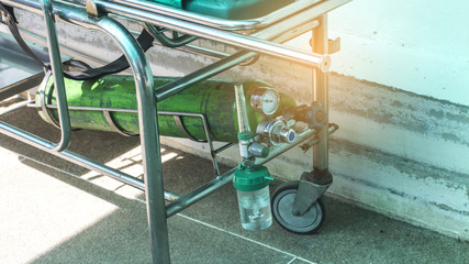 Oxygen cylinder on patient bed.