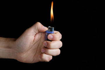 Male hand holding a purple lighter in her fist with a large flame on a black background