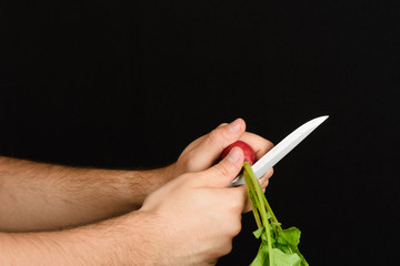 Men's hands cut off tops of radishes on weight, on a black background