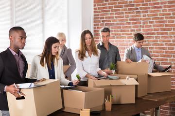 Businesspeople Packing Belongings In Cardboard Box