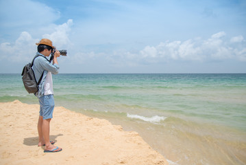 young Asian man photographer with jean shirt and hat taking photo of tropical island beach and turquoise sea, seascape background for summer holiday and vacation travel concepts