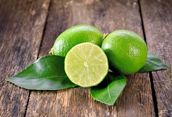 Fresh ripe limes on wooden table.