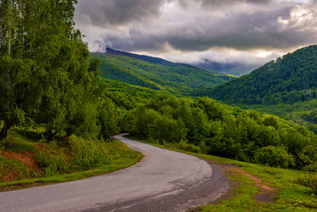 Countryside road in mountains at cloudy sunrise