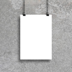 White poster hanging with binder clip on concrete wall background for mock up and design template.
