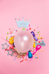 Celebration Flat lay. Candy with colorful party items on pink background.