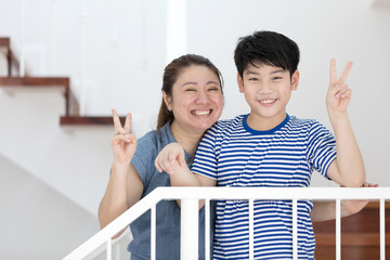 Happy asian mother and son take a photo at home .