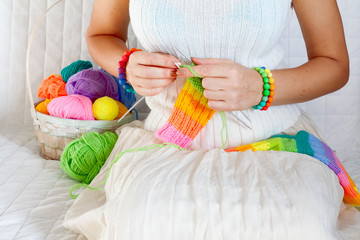 Close-up of woman hands knitting colorful wool yarn. Close-up horizontal photo. Freelance creative working and living concept