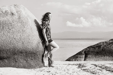attractive young boho girl sitting on the beach