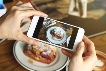 Closeup of women's hands taking photo of sweet dessert by smartphone at coffee cafe.